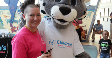 Mascot with participant at Brave the Shave event